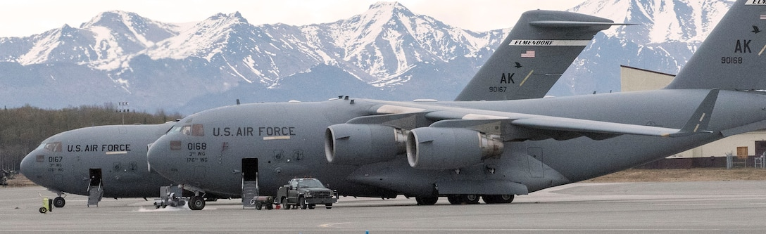 Two C-17 Globe Master III aircraft sit parked on the runway here, Alaska, May 7.