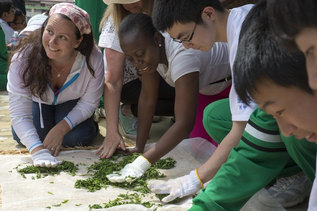 Stefanie Hansen and Tanesha Wallen, Marine Corps Air Station Iwakuni residents, press and roll green tea leaves with Hirose-Iwakuni High School students during a Cultural Adaption Program tea harvesting event in Iwakuni City, May 2, 2017. The Cultural Adaptation Program gave station residents the opportunity to experience the Japanese culture alongside elementary and high school students, nursing home residents and other Japanese locals. (U.S. Marine Corps photo by Lance Cpl. Carlos Jimenez)