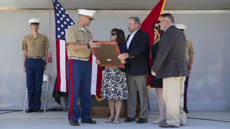 Maj. Chris Cotton, commanding officer of Recruiting Station Montgomery, presents the Navy and Marine Corps Medal to the family of Gunnery Sgt. Thomas Sullivan, at Ross's Landing in Chattanooga, Tenn., May 7, 2017. Cotton is the former Inspector-Instructor for Battery M, 3rd Battalion, 14th Marine Regiment, 4th Marine Division, Marine Forces Reserve, the unit that Sullivan was assigned to.