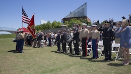 Attendees stand for the posting of the colors during a ceremony posthumously awarding the Navy and Marine Corps Medal to Gunnery Sgt. Thomas Sullivan and Staff Sgt. David Wyatt at Ross's Landing in Chattanooga, Tenn., May 7, 2017. Attendees of the ceremony included Maj. Gen. Burke W. Whitman, commanding general of 4th Marine Division, Sgt. Maj. Michael A. Miller, sergeant major of 4th MARDIV and family members of GySgt Thomas Sullivan and SSgt David Wyatt.