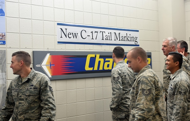 Members of the North Carolina Air National Guard (NCANG) browse the information boards and review the newly unveiled C-17 Globemaster III aircraft tail flash in the dining facility at the NCANG Base, Charlotte Douglas International Airport, May 6, 2017. The tail flash is an integral part of establishing the brand of the NCANG. Every detail from the colors, to the length of the sabre, and the bold print symbolize the importance of new mission that will be carried out by the airmen and C-17 Globemaster III aircraft. (U.S. Air National Guard photo by Staff. Sgt. Laura J. Montgomery)
