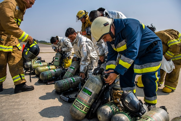 Firefighters from Central America grab their protective gear prior to a live fire exercise about Central America Sharing Mutual Operational and Experience at Joint Task Force – Bravo, Apr. 26, 2017. CENTAM SMOKE is a biannual exercise hosted by Joint Task Force – Bravo with 35 participants from across the 7 Central America nations that includes safety, personal protective equipment, apparatus familiarization, fire hose applications, structural/helicopter live fire evolutions, medical training, vehicle extrication, and aircraft (UH–60/CH–47) egress familiarization, Apr. 24-28, 2017. (U.S. Air National Guard photo by Master Sgt. Scott Thompson/released)