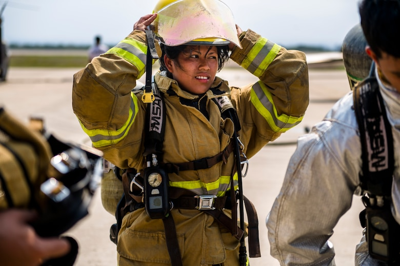 A firefighter from Central America puts on her protective gear prior to a live fire exercise about Central America Sharing Mutual Operational and Experience at Joint Task Force – Bravo, Apr. 26, 2017. CENTAM SMOKE is a biannual exercise hosted by Joint Task Force – Bravo with 35 participants from across the 7 Central America nations that includes safety, personal protective equipment, apparatus familiarization, fire hose applications, structural/helicopter live fire evolutions, medical training, vehicle extrication, and aircraft (UH–60/CH–47) egress familiarization, Apr. 24-28, 2017. (U.S. Air National Guard photo by Master Sgt. Scott Thompson/released)