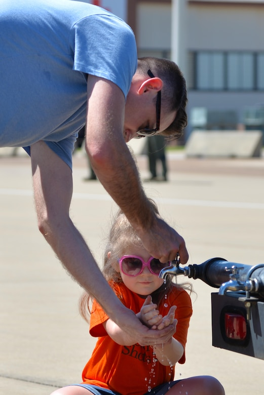 A father helps his daughter wash her hands with water from a portable water tank at the 2017 Defenders of Liberty Airshow on Barksdale Air Force Base, La., May 7. Often referred to as water buffaloes, portable water containers such as these provided attendees with hundreds of gallons of free, clean drinking water throughout the air show. (U.S. Air Force photo//Staff Sgt. Joseph Raatz)