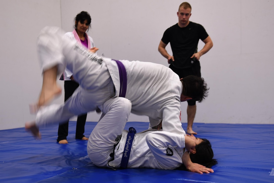 Staff Sgt. Peter Beyer, 19th Civil Engineer Squadron firefighter, and Letia Eclavea, University of Maryland University College student, demonstrate a Brazilian Jiu Jitsu grappling technique April 24, 2017, at the Fitness Center on Little Rock Air Force Base, Ark. Brazilian Jiu Jitsu stimulates the mind, body and spirit while creating social bonds which strengthens the four pillars of Comprehensive Airman Fitness. (U.S. Air Force photo by Airman 1st Class Kevin Sommer Giron)