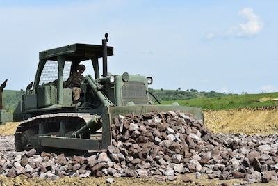 Army Reserve Spc. Jeffrey Nichols, with the 381st Engineer Company, bulldozes rock for a road on the nonstandard live-fire range at the Joint National Training Center in Cincu, Romania, as part of Resolute Castle 17, May 4, 2017. Resolute Castle 17 is an exercise strengthening the NATO alliance and enhancing its capacity for joint training and response. Army photo by Capt. Colin Cutler