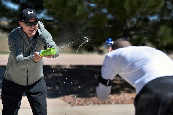 "Chief Master Sgt. Steve Matthews and Staff Sgt. Andrew Skinner, both from the 50th Space Communications Squadron, engage in a water gun fight as part of the ""Amazing gRace"" competition during Wingman Day at Schriever Air Force Base, Colorado, Thursday, May 4, 2017. The event was one of a variety of team-focused activities Airmen engaged in during the day. (U.S. Air Force Photo/Dennis Rogers)"