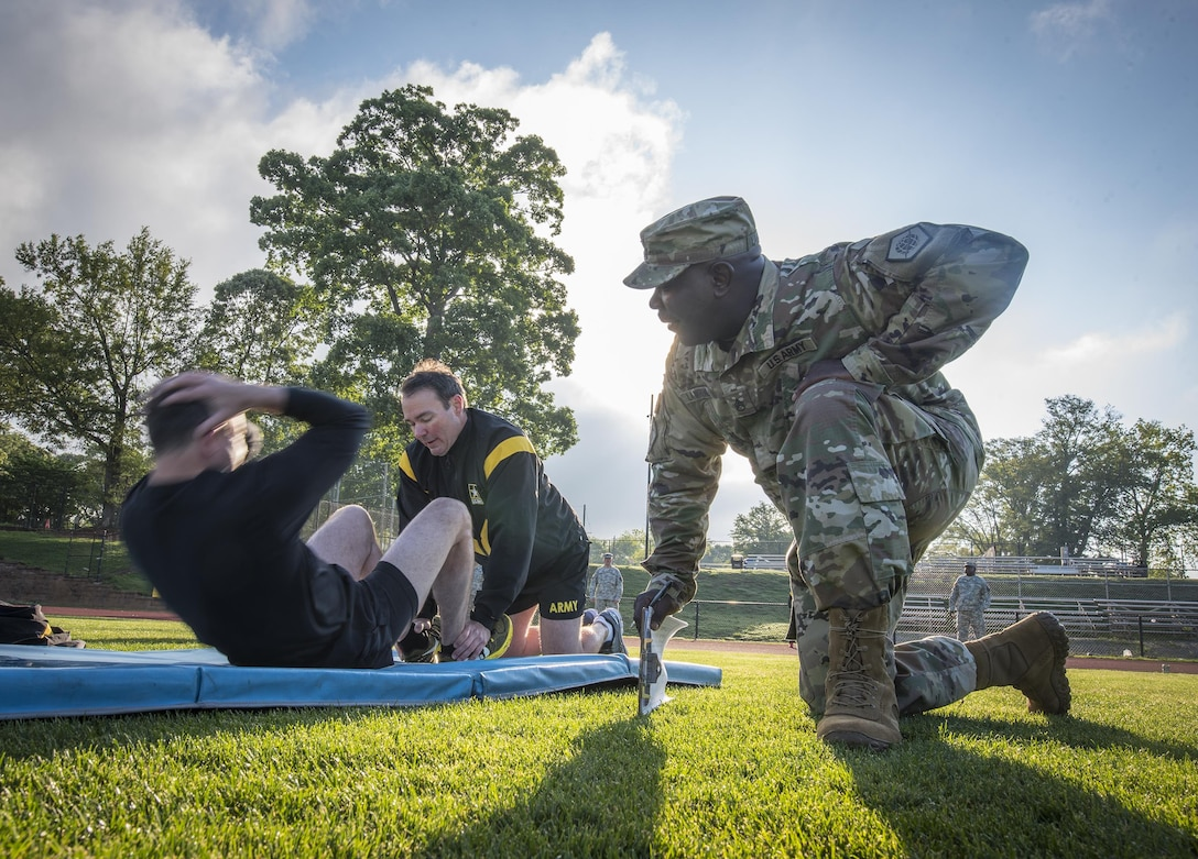 U.S. Army Reserve Staff Sgt. Eddie Lawrence, of Montgomery, Ala., the command ATARS operator for the 335th Signal Command (Theater), grades Master Sgt. Anthony Florence's sit-ups during an Army Physical Fitness Test in East Point, Ga., May 6, 2017. The APFT is designed to test the muscular strength, endurance, and cardiovascular respiratory fitness of soldiers in the Army. Soldiers are scored based on their performance in three events consisting of the push-up, sit-up, and a two-mile run, ranging from 0 to 100 points in each event. (U.S. Army Reserve photo by Staff Sgt. Ken Scar)