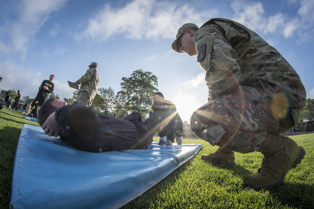 U.S. Army Reserve Sgt. 1st Class Timothy Onderko, of Lawton, Ok., grades Sgt. 1st Class Brent Powell, of Pocahontas, Ark., as Powell does push-ups to pass the Army Physical Fitness Test on a field at Woodward Academy in East Point, Ga., May 6, 2017. The APFT is designed to test the muscular strength, endurance, and cardiovascular respiratory fitness of soldiers in the Army. Soldiers are scored based on their performance in three events consisting of the push-up, sit-up, and a two-mile run, ranging from 0 to 100 points in each event. (U.S. Army Reserve photo by Staff Sgt. Ken Scar)