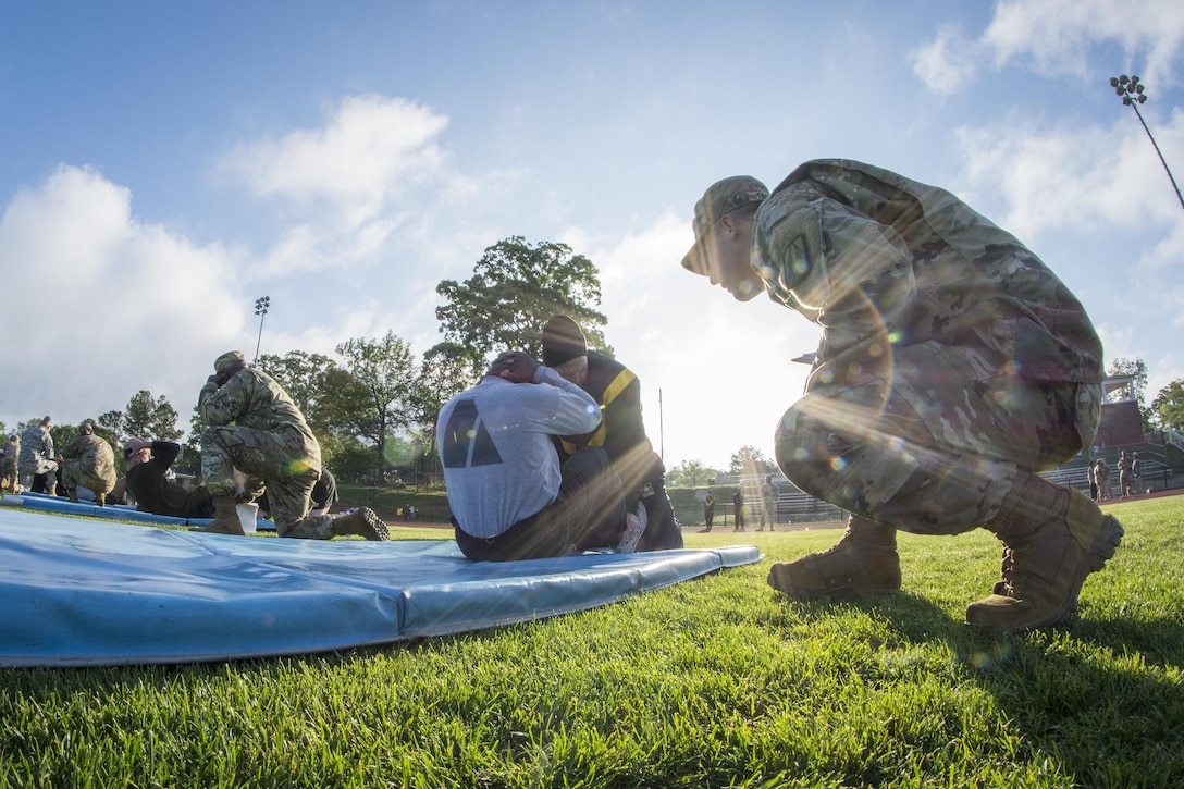 U.S. Army Reserve Sgt. 1st Class Timothy Onderko, of Lawton, Okla., grades Chief Warrant Officer 3 Haile Leaks, of Atlanta, Ga. as Leaks does sit-ups to pass the Army Physical Fitness Test at Woodward Academy in East Point, Ga., May 6, 2017. The APFT is designed to test the muscular strength, endurance, and cardiovascular respiratory fitness of soldiers in the Army. Soldiers are scored based on their performance in three events consisting of the push-up, sit-up, and a two-mile run, ranging from 0 to 100 points in each event. (U.S. Army Reserve photo by Staff Sgt. Ken Scar)
