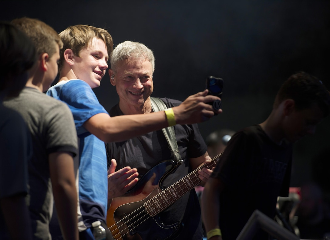 Gary Sinise, bassist for the Lt. Dan Band, takes a photo with MacDill youth during a performance at MacDill Air Force Base, Fla., April 29, 2017. This performance marked the first time the Lt. Dan Band has visited MacDill. (U.S. Air Force photo by Airman 1st Class Adam R. Shanks)