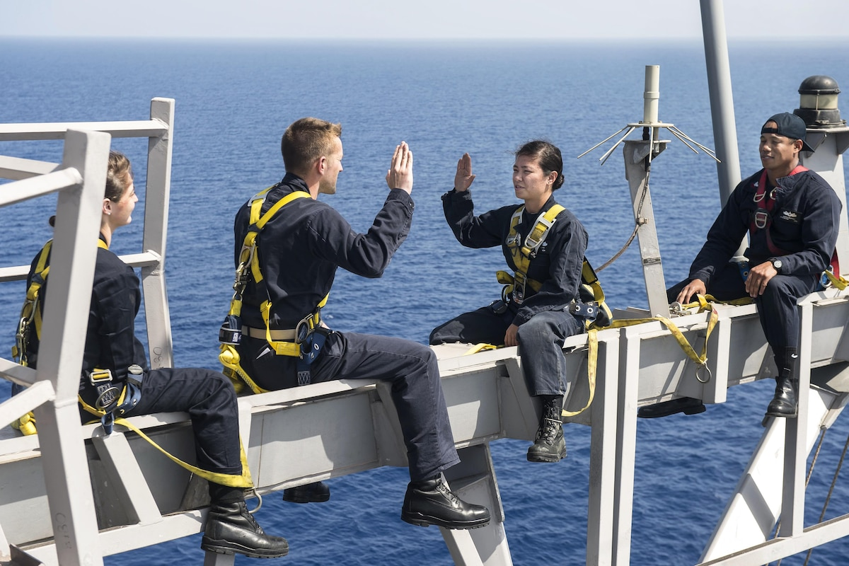 A sailor re-enlists another sailor as they sit on a ship's yardarm.