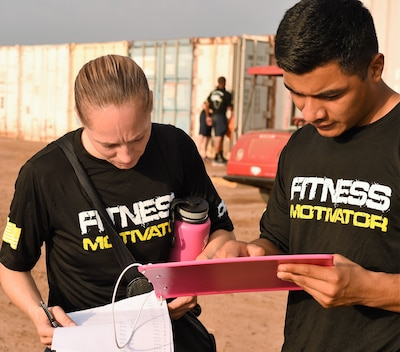 Navy Petty Officer 1st Class Celeste Dunlap, left, Combined Joint Task Force Horn of Africa's command fitness leader, reviews scores with an assistant command fitness leader at Camp Lemonnier, Djibouti, April 28, 2017. Air Force photo by Tech. Sgt. Andria Allmond