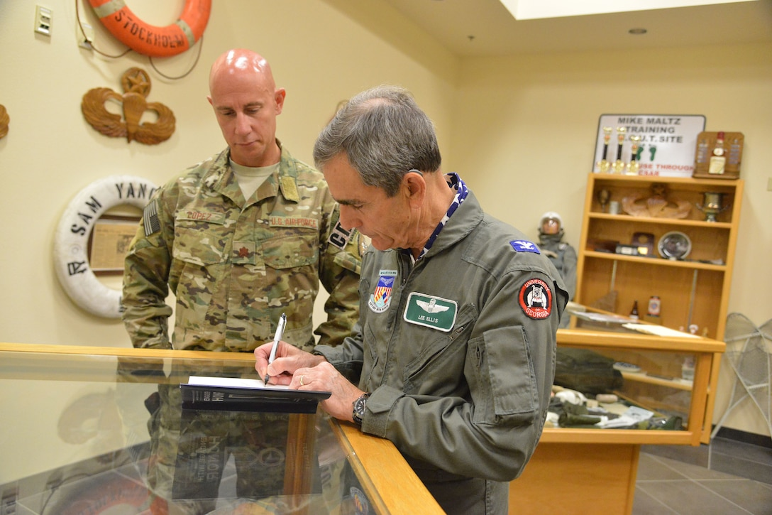 Retired colonel and former Vietnam prisoner of war Lee Ellis autographs his book for Maj. Joseph Lopez, 351st Battlefield Airman Training Squadron commander. Ellis was at Kirtland May 2-3 to speak to the base about the importance of character, courage, commitment in leaders.