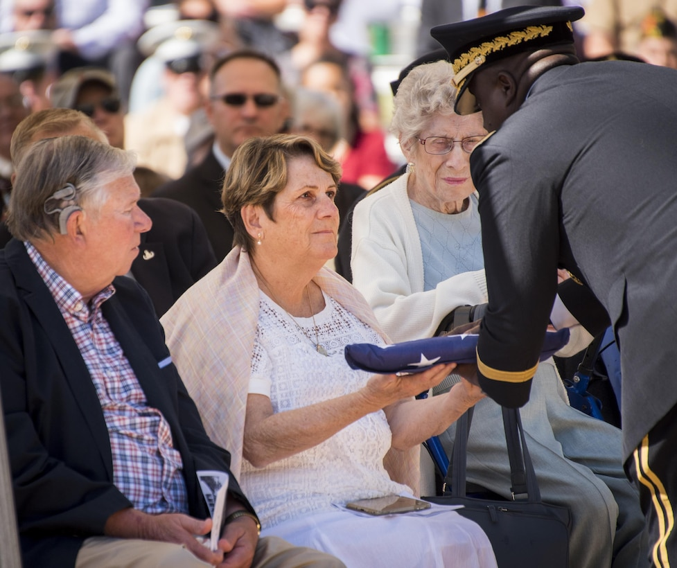 Brig. Gen. David Wilson, U.S. Army Ordnance School commandant, presents a folded flag to Margaret Lauterjung, sister of Army Tech. Sgt. James Eberle, during the 48th Annual Explosive Ordnance Disposal Memorial Service, May 6. Eberle and other names of recent fallen and past EOD technicians are added to the memorial wall during a ceremony each year at the Kauffman EOD Training Complex at Eglin Air Force Base, Fla. The Army and Navy added six new names this year. The all-service total now stands at 326. (U.S. Air Force photo/ Samuel King Jr.)