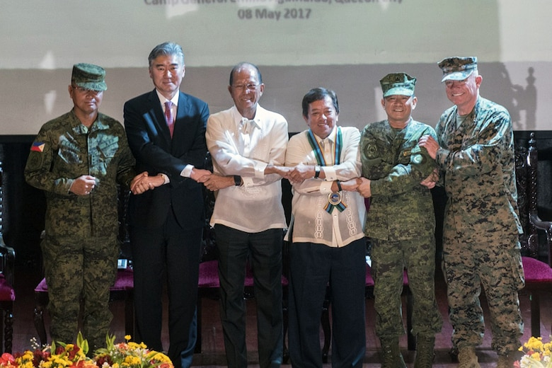 "Armed Forces of the Philippines Lt. Gen. Oscar T. Lacto, left, The Honorable Ambassador Sung Y. Kim, Secretary Delfin N. Lorenzana, Under Secretary Ariel y. Abadilla, AFP Gen. Edruardo M. Año, and U.S. Marine Lt. Gen. Lawrence D. Nicholson stand ""shoulder-to-shoulder"" and shake hands during the opening ceremony for Balikatan 2017 at Camp Aguinaldo, Quezon City, May 8, 2017. Lacto is the Philippine exercise director for Balikatan. Kim is the U.S. Ambassador to the Philippines. Lorenzana is the Philippine Secretary of National Defense. Abadilla is the Philippine Undersecretary for Civilian Security and Consular Concerns. Año is the Chief of Staff of the AFP. Nicholson is the commanding general of III Marine Expeditionary Force. Balikatan is an annual U.S.-Philippine bilateral military exercise focused on a variety of missions including humanitarian and disaster relief, counterterrorism, and other combined military operations."