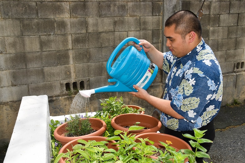 Philip Siu waters his herb garden at the Far East District compound, April 29.