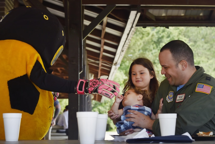 U.S. Air Force Capt. Ricardo Sequeira, right, 628th Medical Group and Flight Surgeon for the 14th Airlift Squadron, and his daughters Sofia, 10 years old, and Maria, one year old, meet the Charleston Battery soccer team mascot during a base picnic at the Air Base Picnic Grounds May 5, 2017, at Joint Base Charleston, S.C. Attendees were provided free meals and were able to participate in various activities including face painting, wall rock climbing, live music and a Military Working Dog demonstration.