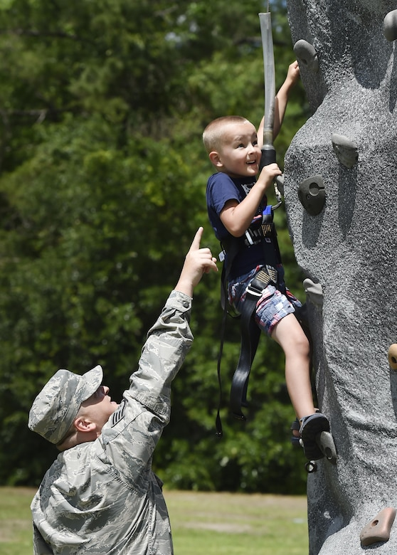 Staff Sgt. Adam Perry, 628th Air Base Wing Safety Office occupational safety specialist, watches his son Wesley, 4 years old, climb a rock wall during a base picnic at the Air Base Picnic Grounds May 5, 2017, at Joint Base Charleston, S.C. Attendees were provided free meals and were able to participate in various activities including face painting, wall rock climbing, live music and a Military Working Dog demonstration.