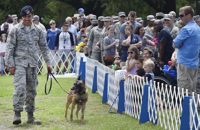 U.S. Air Force Senior Airman Trey Weston, 628th Security Forces Squadron military working dog handler, and Ari, MWD, greet a crowd after performing a demonstration during a base picnic at the Air Base Picnic Grounds May 5, 2017, at Joint Base Charleston, S.C. Attendees were provided free meals and were able to participate in various activities including face painting, wall rock climbing, live music and a Military Working Dog demonstration.