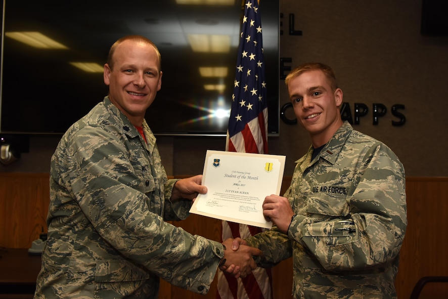 U.S. Air Force Lt. Col. Steven Watts, 17th Training Group deputy commander, presents the 315th Training Squadron Officer Student of the Month award for April 2017 to 2nd Lt. Evan Alban, 315th TRS student, in Brandenburg Hall on Goodfellow Air Force Base, Texas, May 5, 2017. (U.S. Air Force photo by Airman 1st Class Caelynn Ferguson/Released)