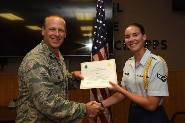 U.S. Air Force Lt. Col. Steven Watts, 17th Training Group Deputy Commander, presents the 312th Training Squadron Student of the Month award for April 2017 to Airman 1st Class Claire Newman, 312th TRS student, in Brandenburg Hall on Goodfellow Air Force Base, Texas, May 5, 2017. (U.S. Air Force photo by Airman 1st Class Caelynn Ferguson/Released)