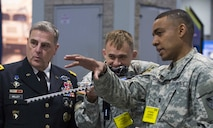"""Capt. Brent Chapman (right) and Capt. Frederick """"Erick"""" Waage (center) show Gen. Milley (left) their cyber """"maker"""" creation of a prototype cyber """"rifle"""" which allows them to disable drones from a distance."""