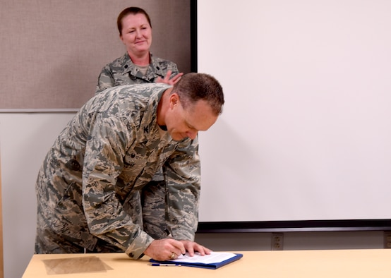 Col. Jeffery White, 377th Medical Group commander, signs a proclamation for National Nurses and Medical Technicians Week at a ceremony at the Health Clinic May 8. The ceremony honored the group's nurses and technicians for their contributions to world-class healthcare.