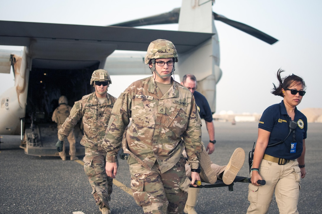 Pfc. Perry Wolf and Dylan Pulos, combat medics with the 86th Combat Support Hospital, as well as Jane Rivera, an Emergency Medical Technician with Area Support Group - Kuwait, Joint Emergency Service, move a simulated casualty off of a MV-22 Osprey, during a joint training exercise with Marines from Marine Medium Tiltrotor Squadron - 364 (VMM-364), at Camp Arifjan, Kuwait, May 8, 2017. (U.S. Army Photo by Sgt. Christopher Bigelow)