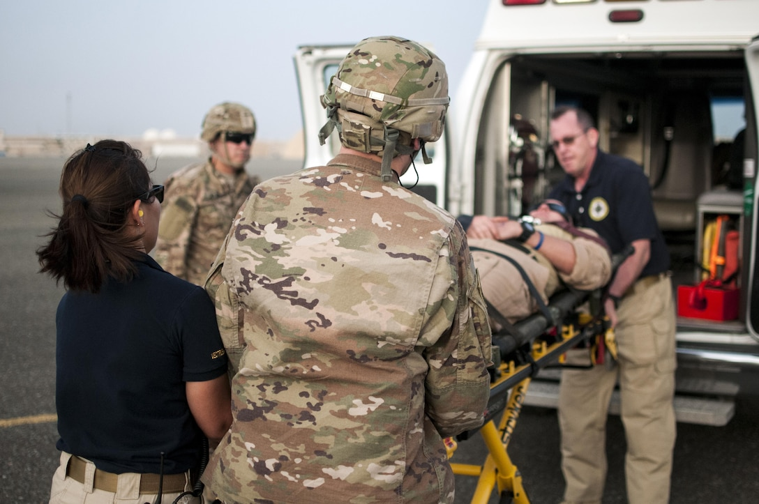 U.S. Army combat medics, with the 86th Combat Support Hospital, and Emergency Medical Technicians, with Area Support Group - Kuwait, Joint Emergency Service, move a simulated casualty onto an ambulance, during a joint training exercise with Marines from Marine Medium Tiltrotor Squadron - 364 (VMM-364), at Camp Arifjan, Kuwait, May 8, 2017. (U.S. Army Photo by Sgt. Christopher Bigelow)
