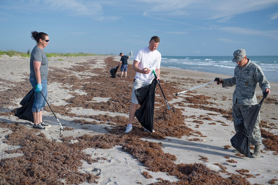 Ericka Barnes, Tech. Sgt. Ryan Bush, and 1st Lt. Joshua Kreimier, of the 45th Space Wing Inspector General's Office, remove litter from the shoreline as part of Earth Day activities, April 20, 2017, at Cape Canaveral Air Force Station, Fla. The 45th Space Wing celebrated Earth Day with multiple events to include a tree planting ceremony to honor the memory of the late retired Senior Master Sgt. Arthur Fetskos and his many years of service. (U.S. Air Force photo by Matthew Jurgens)