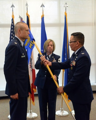 Col. Jim P. Duong (right), 132d Wing (132 WG) outgoing Medical Group (MDG) commander and Col. Shawn D. Ford (left), commander 132 WG, exchange the 132 WG MDG guidon during the change of command ceremony at the 132 WG MDG, Des Moines, Iowa on May 7, 2017. This action formally recognized Duong passing over the MDG commander role. (U.S. Air National Guard photo by Airman 1st Class Katelyn Sprott)