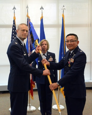 Col. Jim P. Duong (right), 132d Wing (132 WG) outgoing Medical Group (MDG) commander and Col. Shawn D. Ford (left), commander 132 WG, pose for a photo during the exchange of the 132 WG MDG guidon during the change of command ceremony at the 132 WG MDG, Des Moines, Iowa on May 7, 2017. This action formally recognized Duong passing over the MDG commander role, where he served for five years. (U.S. Air National Guard photo by Airman 1st Class Katelyn Sprott)