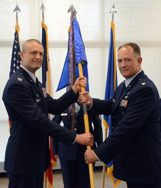 Lt. Col. Chad M. Hynnek (right), 132d Wing (132 WG) incoming Medical Group (MDG) commander and Col. Shawn D. Ford (left), commander 132 WG, pose for a photo during the exchange of the 132 WG MDG guidon during the change of command ceremony at the 132 WG MDG, Des Moines, Iowa on May 7, 2017. This action formally recognized Hynnek accepting the MDG commander role, Hynnek is the 10th commander of the MDG. (U.S. Air National Guard photo by Airman 1st Class Katelyn Sprott)