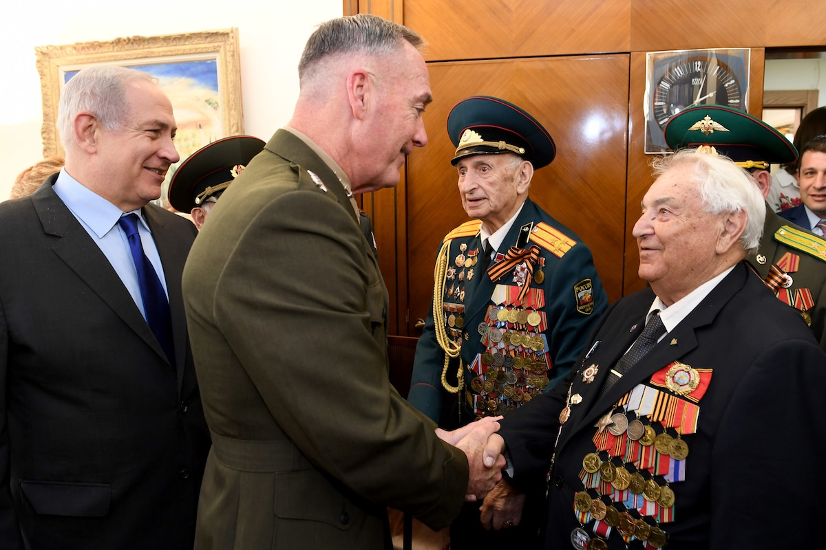 Marine Corps Gen. Joe Dunford, chairman of the Joint Chiefs of Staff, shakes hands with a veteran wearing medals.