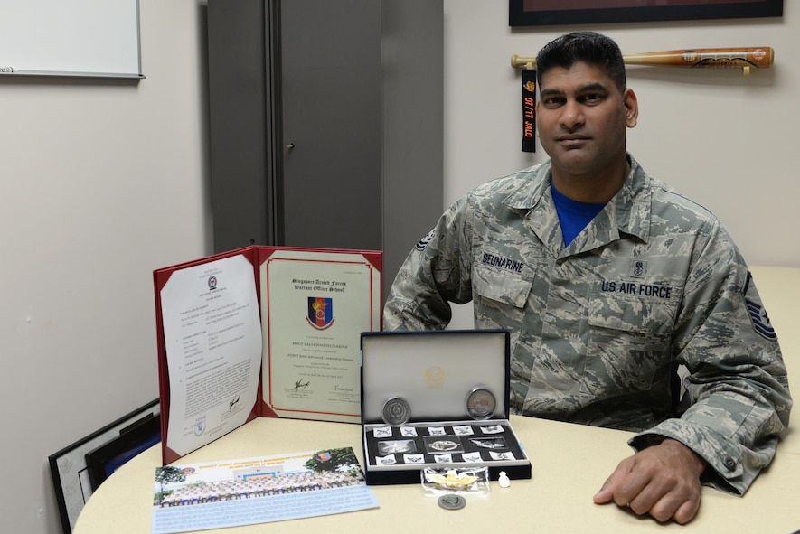 U.S. Air Force Master Sgt. Lallchan Seunarine, the 354th Medical Operations Squadron public health flight chief, poses with items from the Singapore Enlisted Officer Training Course May 5, 2017, at Eielson Air Force Base, Alaska. Seunarine's syndicate team presented him with several items to memorialize their time learning together. (U.S. Air Force photo by Airman 1st Class Cassandra Whitman)
