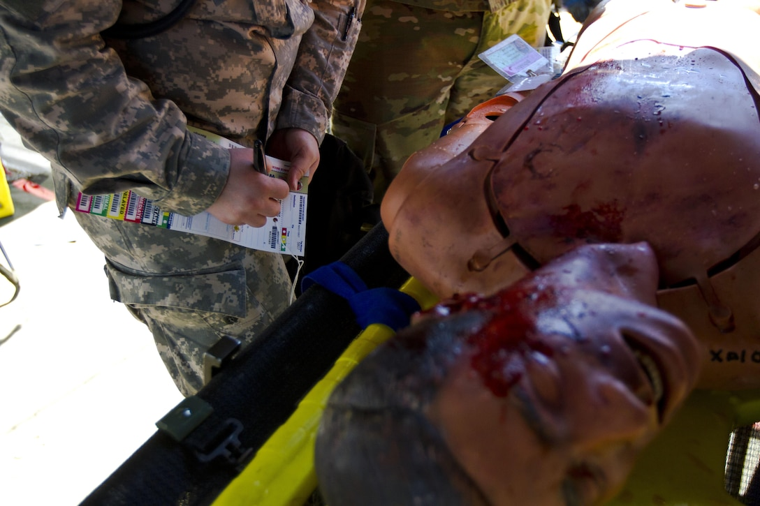 U.S. Army Reserve Soldiers assigned to the 409th Medical Company out of Madison, Wis., examine a casualty during Vibrant Response 17 at Camp Atterbury, Ind., May 7, 2017. The 409th Medical Company is assigned to Task Force 76 as one of their immediate medical care units. Vibrant Response 17 is an annual command post exercise that simulates the detonation of a nuclear bomb in a major city within the United States. This year it was integrated with Guardian Response 17 at Muscatatuck Urban Training Center, Indiana. The exercises enable emergency response organizations, both civilian and military, to integrate and provide relief during a catastrophic disaster. (U.S. Army Reserve Photo by Sgt. Stephanie Ramirez)