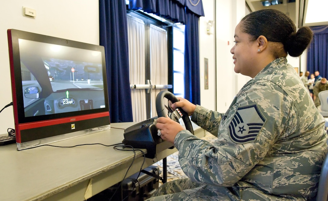 "Master Sgt. Chandra Hines, 436th Aerospace Medicine Squadron, drives a vehicle simulator May 5, 2017, at The Landings on Dover Air Force Base, Del. At Dover's Wingman University ""You booze, you cruise, you lose"" activity, Hines and other Team Dover members attempted to navigate a vehicle through a road course that simulated driving under the influence. (U.S. Air Force photo by Roland Balik)"