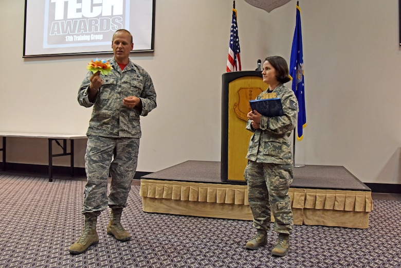 U.S. Air Force Lt. Col. Steven Watts II, 17th Training Group Deputy Commander, asks Tech. Sgt. Cheyanne Samples, 315th Training Squadron instructor, about the paper flower she used in the Top Tech competition at the Event Center on Goodfellow Air Force Base, Texas, May 5, 2017. Watts announced Samples as the best instructor of the 17th TRG for the first quarter. During the competition, instructors had to teach a subject and audience members had to demonstrate their understanding of the topic. (U.S. Air Force photo by Staff Sgt. Joshua Edwards/Released)