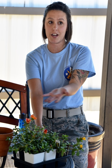 U.S. Air Force Staff Sgt. Rebekka Thompson, 316th Training Squadron instructor, repots a plant at the Top Tech competition outside the Event Center on Goodfellow Air Force Base, Texas, May 5, 2017. Thompson taught about the proper care of a Moss Rose for her presentation. During the competition, instructors had to teach a subject and audience members had to demonstrate their understanding of the topic. (U.S. Air Force photo by Staff Sgt. Joshua Edwards/Released)