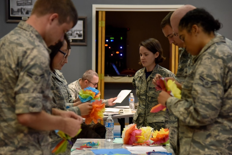U.S. Air Force Tech. Sgt. Cheyanne Samples, 315th Training Squadron instructor, watches Airmen make paper flowers for the Top Tech competition at the Event Center on Goodfellow Air Force Base, Texas, May 5, 2017. Samples taught the Airmen the skills needed to make flowers without assistance. During the competition, instructors had to teach a subject and audience members had to demonstrate their understanding of the topic. (U.S. Air Force photo by Staff Sgt. Joshua Edwards/Released)