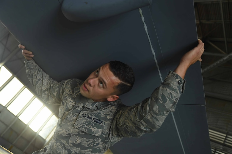 Senior Airman Paulino holds an MQ-9 Reaper model wing steady while a team of seven airmen with the 432nd Maintenance Squadron insert it into the fuselage of the display. The maintenance crew was tasked with unloading, building and maintaining the model for the 2017 Wings over Solano air show. (U.S. Air Force photo/Airman 1st Class James Thompson)