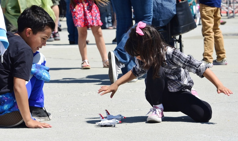 Gabriel, nine, and Sofia, five, children of Mariano Hernandez, a Sacramento local and U.S. Navy veteran, play with U.S. Air Force Thunderbird toys during the Wings Over Solano air show May 7, 2017, at Travis Air Force Base, Calif. The event attracted more than 100,000 guests and featured performances by the U.S. Army Golden Knights and the Air Force Thunderbirds. (U.S. Air Force photo/Senior Airman Christian Clausen)