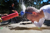 """Staff Sgt. Andrew Skinner, 50th Space Communications Squadron, endures one of the Amazing gRace physical challenges at Schriever Air Force Base, Colorado, Thursday, May 4, 2017.  The virtue of this event was """"courage"""" as team members had to face the wrath of Super Soaker attacks to pass the challenge.  (U.S. Air Force Photo/Dennis Rogers)"""