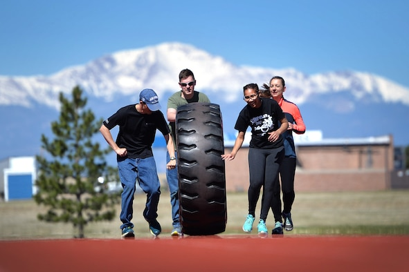 "Amazing gRace participants, Elisha Patterson, Scott Balcao, Emily Schultz and Jordan Fobes, team name ""The Misfits,"" roll a tractor tire on the running track to complete one of their challenges at Schriever Air Force Base, Colorado, Thursday, May 4, 2017.  This team came together at the 11th hour to participate in the Amazing gRace, but finished strong despite being strangers. (U.S. Air Force photo/Dennis Rogers)"