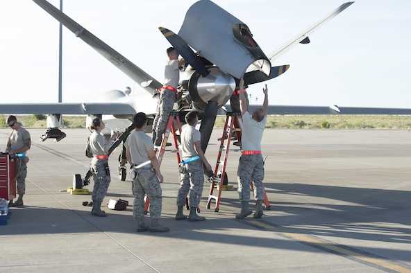 49th Aircraft Maintenance squadron Airmen hoist an engine cover panel onto an MQ-9 at Holloman Air Force Base, N.M., May 4, 2017. Holloman AFB conducted surge operations from May 1 to May 5, ramping up operations to accurately measure the full capability of its Airmen and equipment.