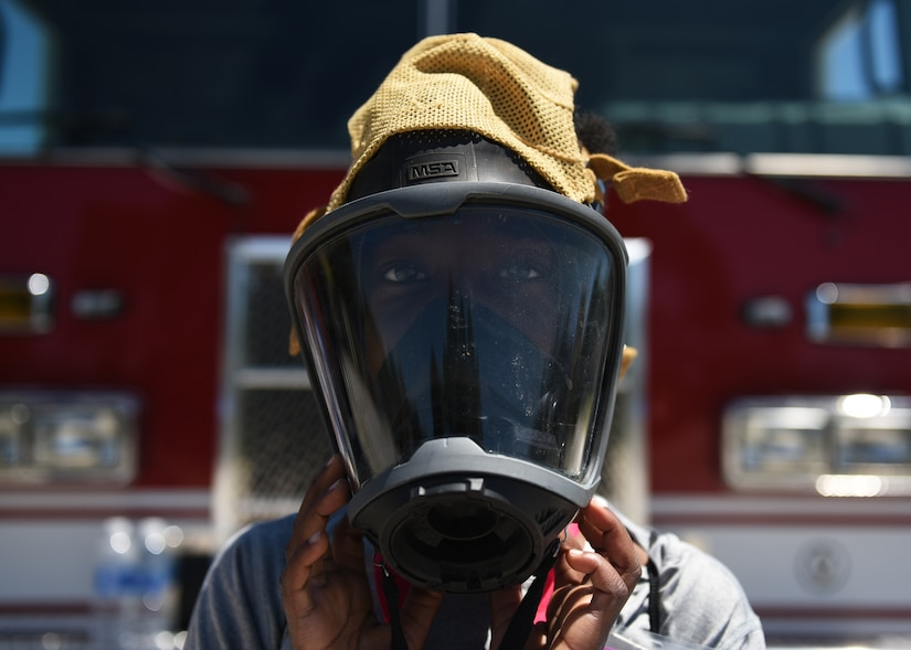 Sidney Dew, a Tyndall Jr. Raptor participant, tries on a protective mask used by firefighters at the Tyndall Air Force Base, Fla., Silver Flag site, May 6, 2017. Dew was one of 63 children who had the opportunity to experience what it is like to walk in a military member's boots as part of the annual Jr. Raptor program. Air Force photo by Senior Airman Sergio A. Gamboa