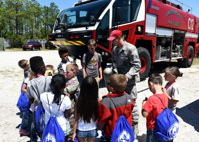 Children participating in the Tyndall Jr. Raptor program hosted by the 325th Force Support Squadron Youth Center receive a briefing on firefighter equipment at the Tyndall Air Force Base, Fla., Silver Flag site, May 6, 2017. Air Force photo by Senior Airman Sergio A. Gamboa