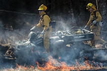 Firefighting personnel, assigned to the 673rd Civil Engineer Squadron, conduct a controlled burn at the Infantry Platoon Battle Course on Joint Base Elmendorf-Richardson, Alaska, May 4, 2017. JBER Fire Department and U.S. Forest Service personnel worked together to manage the prescribed fires. Controlled burns consume accumulated dry brush and grass thereby reducing the risk of wildfires. (U.S. Air Force photo/Alejandro Pena)