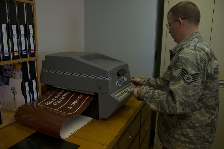 Staff Sgt. Horace Hand, 5th Civil Engineer Squadron structural craftsman, prints a sign at the sign shop on Minot Air Force Base, N.D., April 27, 2017. Thermal printers are used to produce images by selectively heating coated paper when passed over the print head. (U.S. Air Force photo/Airman 1st Class Dillon Audit)